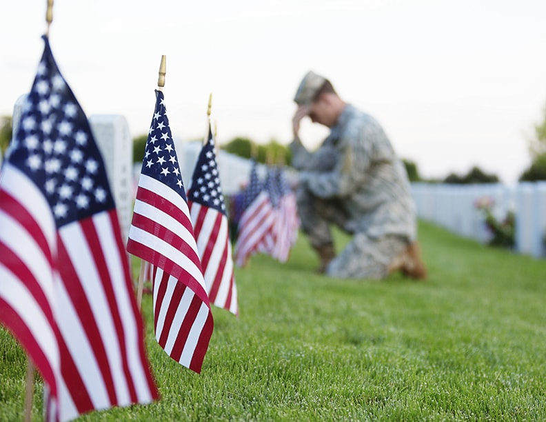 Soldier kneeing at a grave on flag day