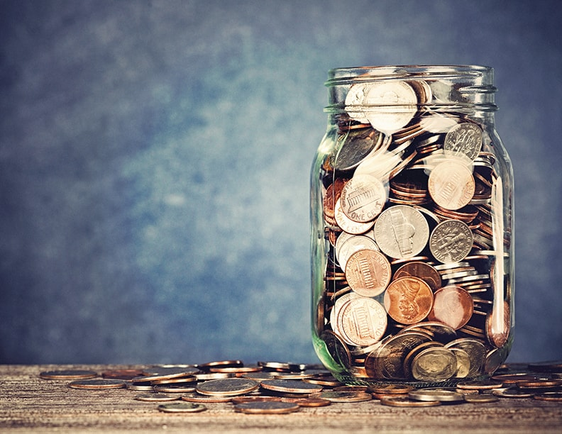 A mason jar filled with coins.