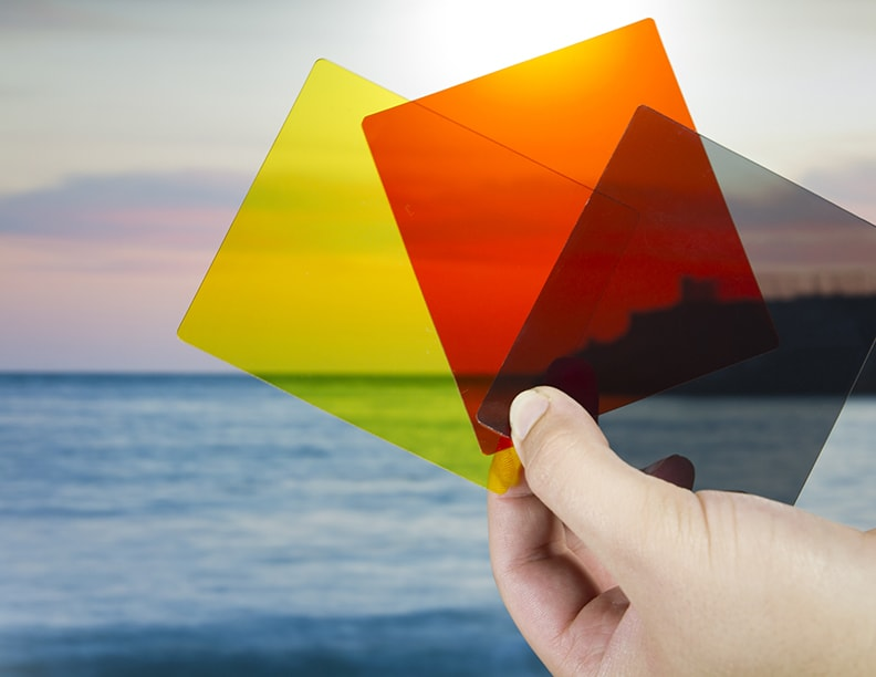 A hand holding three colored lens.