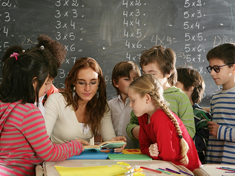 Children gathered around a school teacher